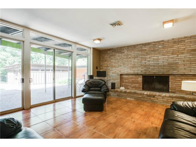 Lower level living area features large brick fireplace and a wal