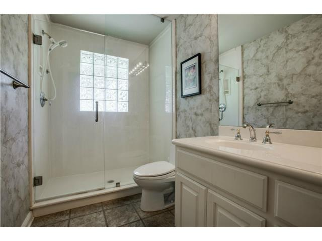 Hall guest bath has large walk in shower with glass block window
