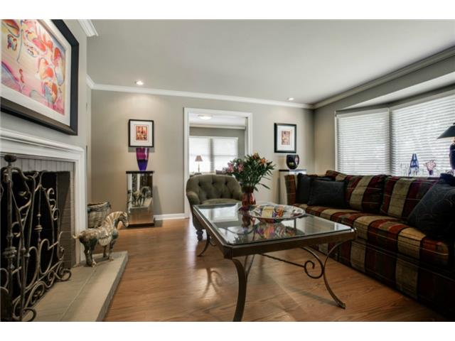 The formal living room features a gas fireplace, laminate wood f