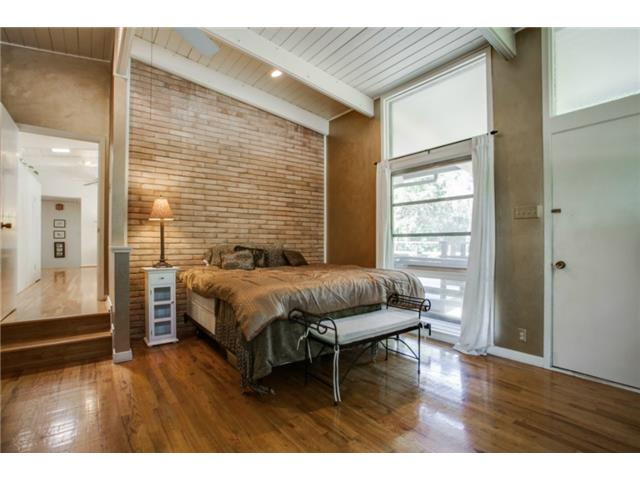 Master Bedroom with exposed brick wall and door leading to deck