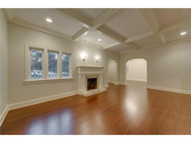Living room with original windows, hardwood floors, fireplace an