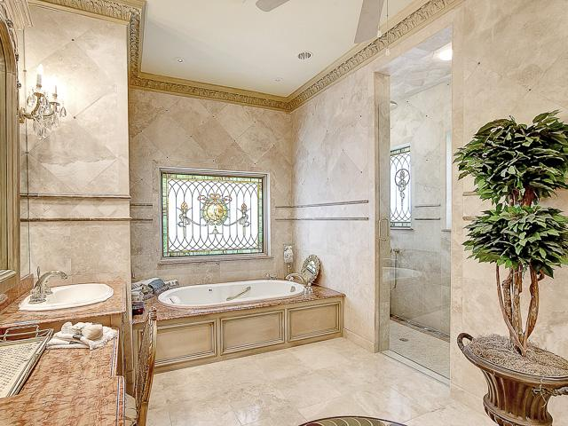 Master Bath has Jacuzzi tub, stai glass windows, marble vanities