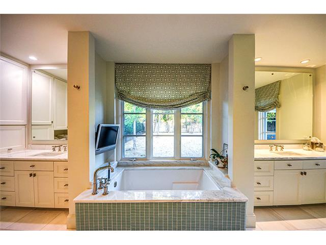 The master bath is truly a home spa. Vanities are separated by a
