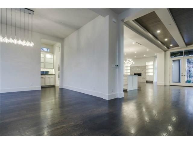 Open floor plan with handsome ceiling treatments and oak floors