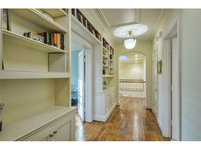 The wide second floor hallway furnished with built-in bookshelve