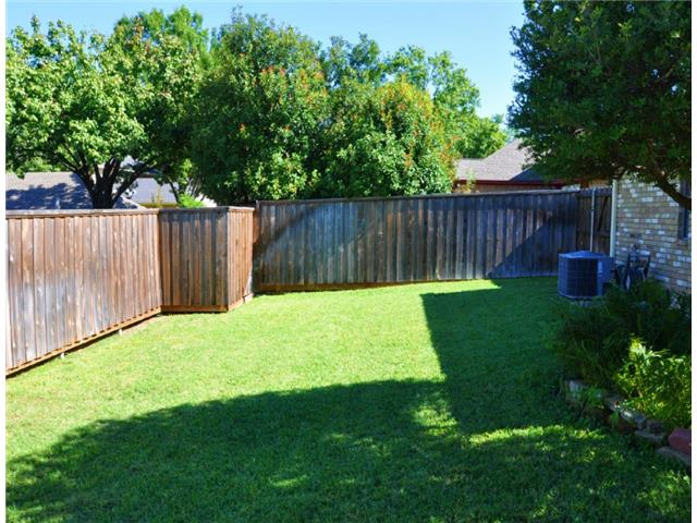 Lush green grass abounds in this back yard with a privacy fence