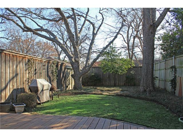 Fenced back yard with mature tree
