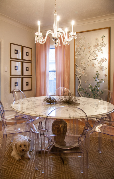 "The modern ""Ghost"" chairs, paired with a vintage marble-topped table and crystal chandelier, makes a visually interesting combination in the dining room."
