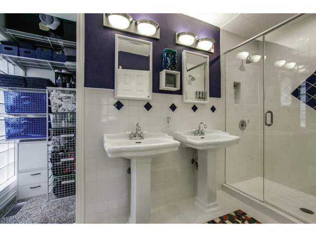 The master bath is clean and crisp with white tile and custom ti