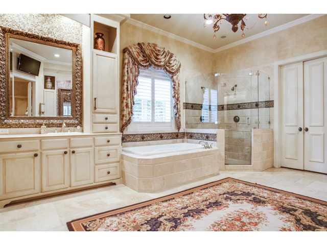 Updated master bath offers travertine floors, separate shower wi