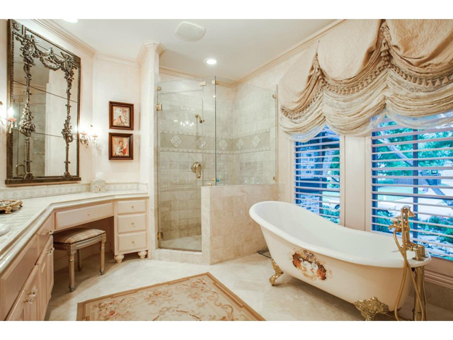 Exceptionally updated en-suite bathroom offers a gold claw antiq
