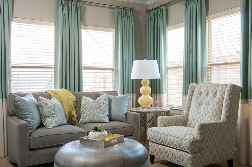 The sitting area of the master suite already had an abundance of natural sunlight from the windows, so Gilbert added custom stationary drapery panels, mostly neutral furniture pieces, and pops of yellow with the lamp and accessories.