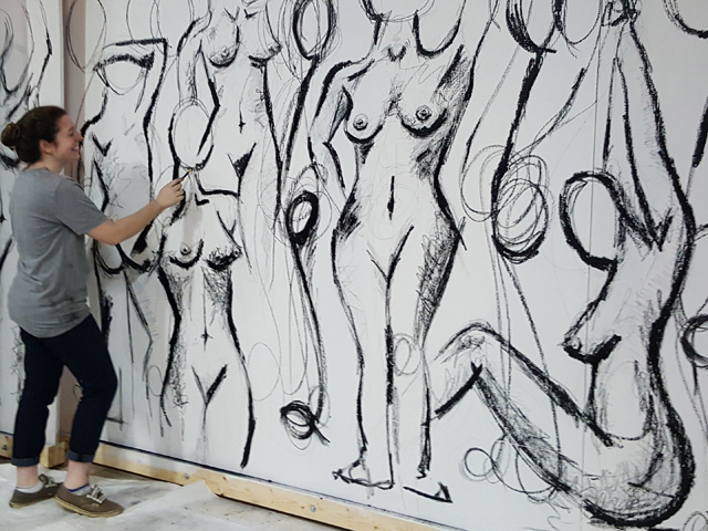 Artist Meagan Cope works on a mural featured in the