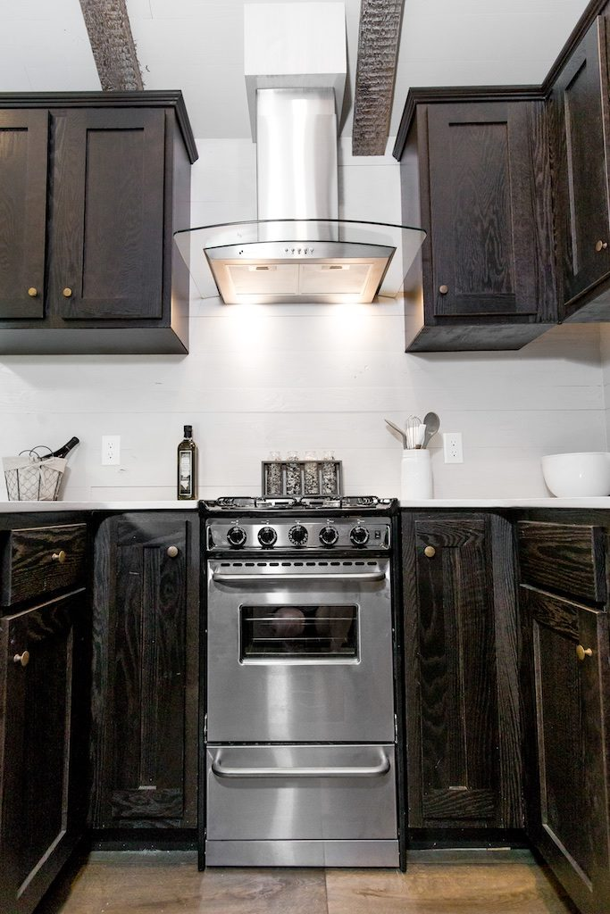 The Clayton Tiny Home features a kitchen with ample cabinets and fully functioning appliances by Summit