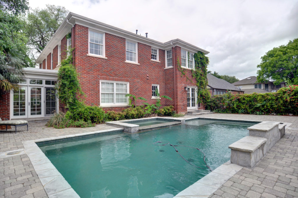 Paver motor court surrounds pool, garage and guest house.