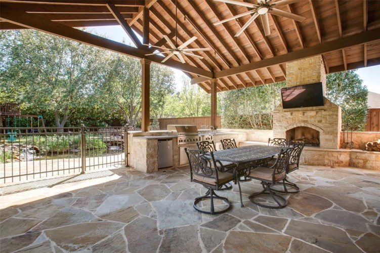 Escape to an oasis on your flagstone covered patio complete with outdoor kitchen and fireplace.